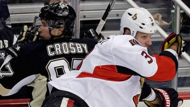 Sidney Crosby of Pittsburgh and Ottawa defenceman Marc Methot battle during a regular season game.