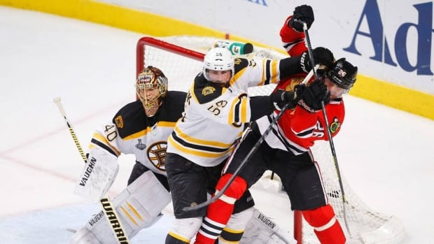 Boston Bruins defenceman Johnny Boychuk (55) battles with Chicago Blackhawks forward Michal Handzus (26) as Bruins goalie Tuukka Rask tries to see the play during Game 2 of the Stanley Cup final on Saturday.