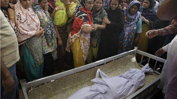 Pakistani women mourn next to the body of a child, who killed in Saturday's bombing, during a funeral in Karachi on Sunday, one of several bombings in the country in recent days ahead of national elections.