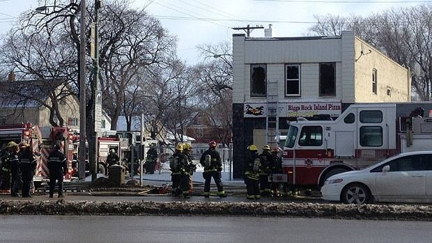 Fire crews clean up after a fire at a business on the corner of Main Street and Burrows Avenue in Winnipeg on Tuesday.