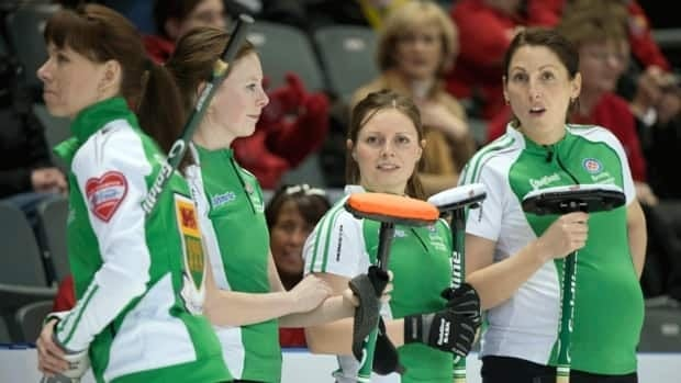 Team Saskatchewan's Kara Johnston, right, who is seven months pregnant, chats with teammates during her rink's game against the Northwest Territories at the Scotties Tournament of Hearts in Kingston, Ont., on Saturday.
