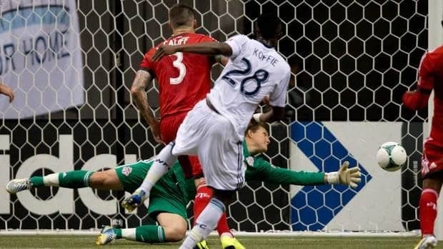Vancouver Whitecaps' Gershon Koffie scores the only goal of the game against Toronto FC goalkeeper Joe Bendik, back, as Danny Califf, left, looks on during the second half in Vancouver, B.C., on Saturday.