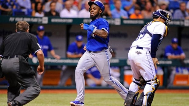 Toronto Blue Jays' Jose Reyes, centre, scores ahead of Tampa Bay Rays catcher Jose Lobaton, right, after advancing off of Edwin Encarnacion's single during the fifth inning on Friday in St. Petersburg, Florida.