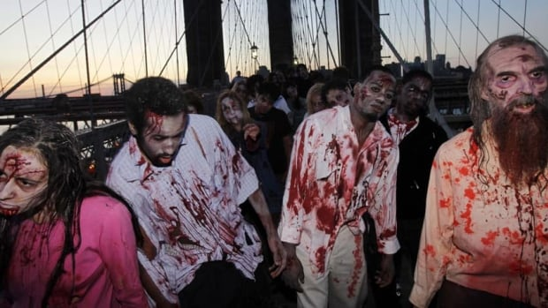Costumed actors, promoting the television series The Walking Dead, shamble along the Brooklyn Bridge. Clemson University English professor Sarah Lauro says people are more interested in zombies when they're dissatisfied with society as a whole.