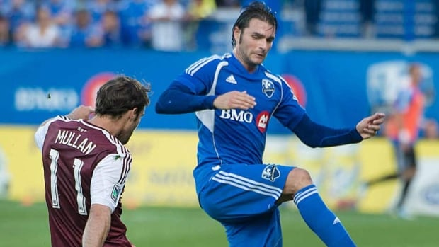 Montreal Impact's Andrea Pisanu tries to block a pass by Colorado Rapids' Brian Mullan in Montreal on Saturday.