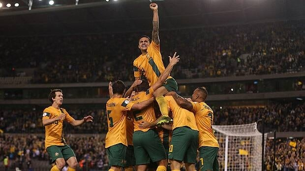 Tim Cahill climbs the pile as the Australians celebrate after captain Lucas Neill of the Socceroos scored against Jordan at Etihad Stadium in Melbourne on Tuesday.