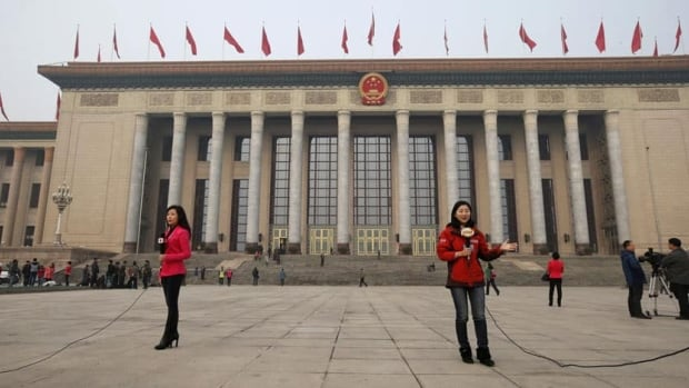 Journalists report in front of the Great Hall of the People during the closing session of the National People's Congress in Beijing March 17, 2013.