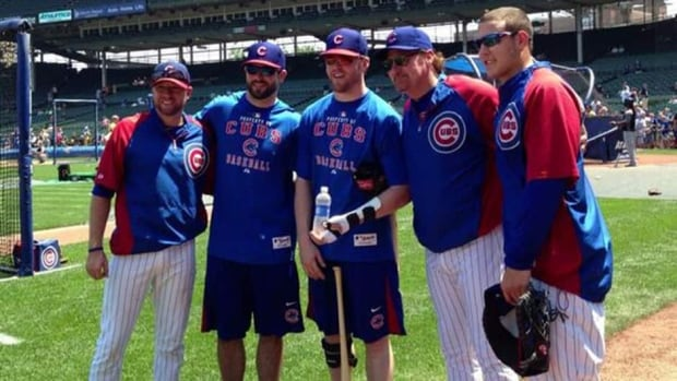 Teammates from the Stanley Cup champion Blackhawks Brandon Bollig, second from left, and Bryan Bickell, centre, pose with Cubs rookie Anthony Rizzo, right, at Wrigley Field in Chicago on July 5. Bollig and Bickell were on hand to take part in batting practice with the MLB team.