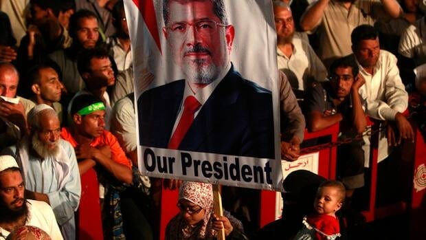 A supporter of deposed Egyptian president Mohammed Morsi holds a banner while taking part in a protest at the Rabaa Adawiya square, where supporters are camping, in Cairo.