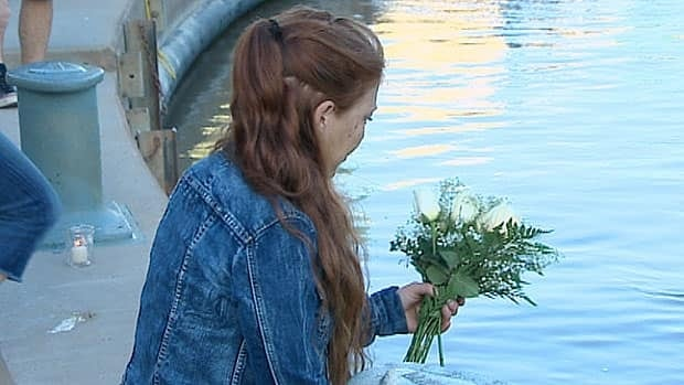 Some 200 people gathered at The Forks in Winnipeg Thursday night to place flowers into the river as part of a vigil to Lisa Gibson and her two children.