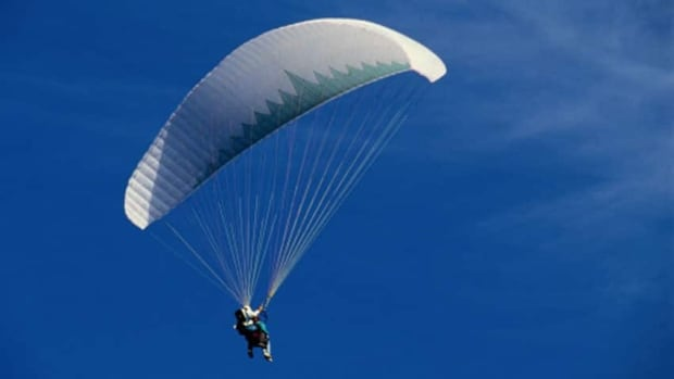 Paragliding is a recreational and competitive sport where the pilot sits in a harness attached to a fabric wing.