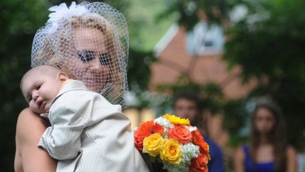 Christine Swidorsky carries her son and the couple's best man, Logan Stevenson, 2, down the aisle to her husband-to-be Sean Stevenson during the wedding ceremony in Jeannette, Pa., on Saturday. Logan died on Monday.