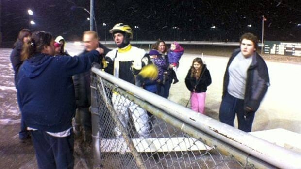 Driver Paul Maclean hands his whip to the crowd after winning a race on the final night at Sudbury Downs.