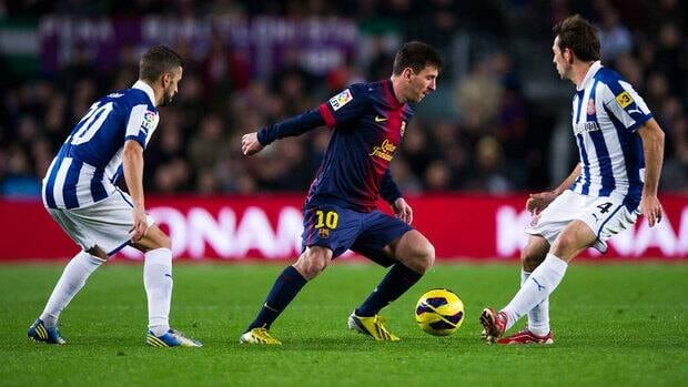 Messi of Barcelona, centre, duels for the ball with Simao Sabrosa, left, and Victor Sanchez of Espanyol during their match Sunday.