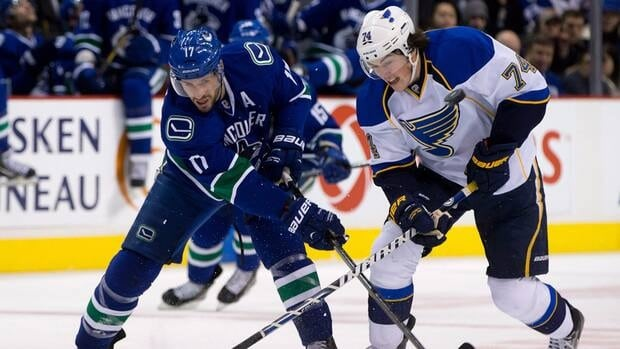 Vancouver Canucks' Ryan Kesler, left, and St. Louis Blues' T.J. Oshie vie for control of the puck on Sunday February 17, 2013.