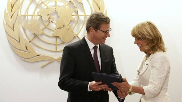 German Foreign Minister Guido Westerwelle presents the United Nations Arms Trade Treaty to Under-Secretary-General for Legal Affairs and United Nations Legal Counsel at the United Nations headquarters in New York. Canada wants to consult before signing the deal, the foreign minister says.