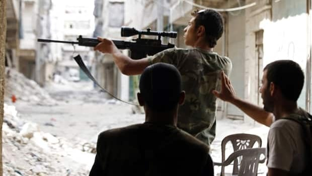 A Free Syrian Army fighter points his weapon during clashes with forces loyal to Syria's President Bashar al-Assad in Aleppo's al-Amereya district on Monday.