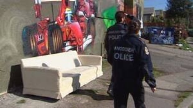 Police investigate the scene in October 2009 where a man was assaulted and burned while lying on a discarded couch.