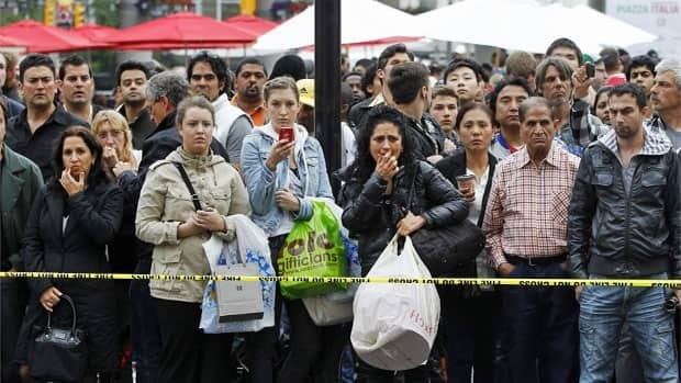 Bystanders stand outside the Toronto Eaton Centre shopping mall after a Saturday evening shooting left one man dead and seven others injured.