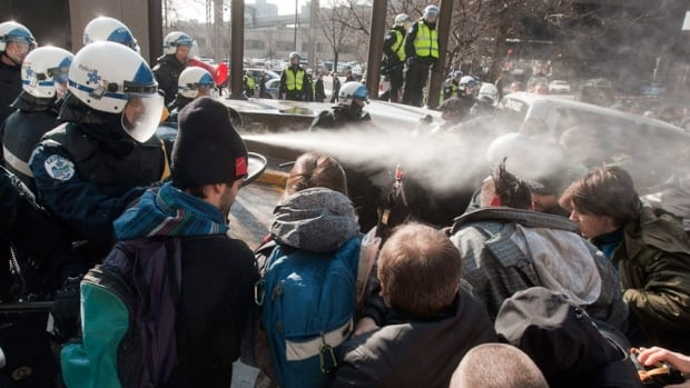 Police use pepper spray to disperse a crowd blocking the Delta hotel during a student demonstration in February. With some classes resuming next week, Montreal police say they won't intervene against campus protests that violate Bill 78 unless asked to do so by school authorities.