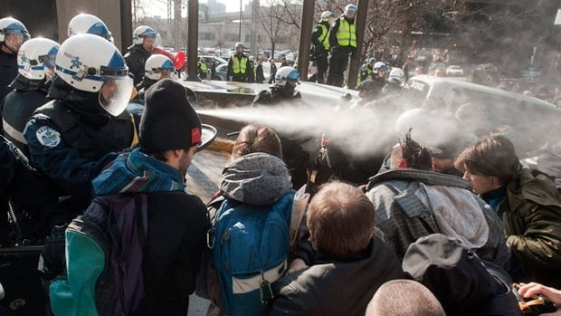 Police use pepper spray to disperse a crowd blocking the Delta hotel during a demonstration against higher tuition fees Thursday, February 16, in Montreal.
