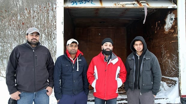 Members of the Stoney Creek Cricket Academy stand in front of their equipment trailer, located on an east Hamilton field. They visited their trailer on Christmas Day, only to find that most its contents had been stolen or damaged.