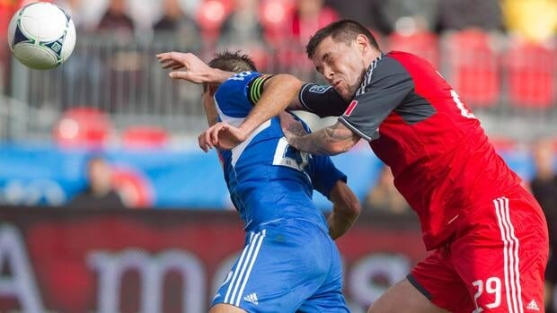 Toronto FC 's Eric Hassli, right, sends a header just wide of the Montreal goal despite the efforts of the Impact's Davy Arnaud in Toronto on Saturday October 20, 2012 in Toronto.