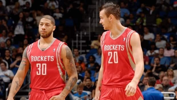 Royce White, left, of the Houston Rockets and teammate Donatas Motiejunas, right, confer during a game against the Orlando Magic on October 26, 2012 at Amway Center in Orlando, Florida.