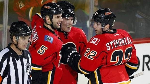 Calgary Flames' Mike Cammalleri, centre, celebrates his game winning goal with teammates Mark Giordano, left, and Lee Stempniak during the thirs period of their game agianst the Vancouver Canucks Thursday. The Flames beat the Canucks 3-2.