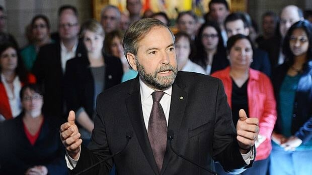 NDP Leader Tom Mulcair speaks to reporters with his MPs behind him following the last caucus meeting before the summer break.