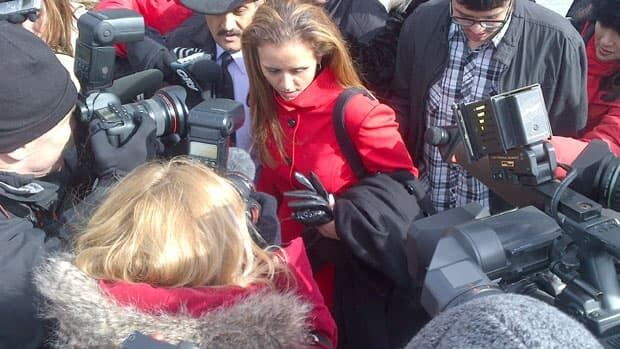 Darwin's owner, Yasmin Nakhuda, moves through a crowd of reporters outside the court in Oshawa, Ont.