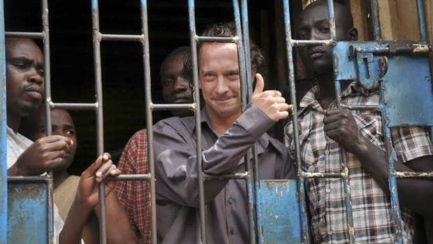 David Cecil, centre, is shown in a Ugandan jail cell in September 2012. The British producer of the play The River and the Mountain has been deported from Uganda.