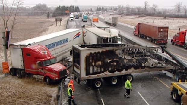 Emergency crews work to move transport trucks that collided early Thursday morning.