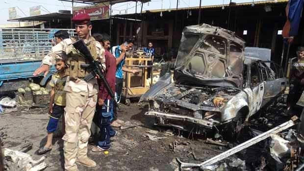 An Iraqi soldier inspects the site of the bomb attack in Kerbala.