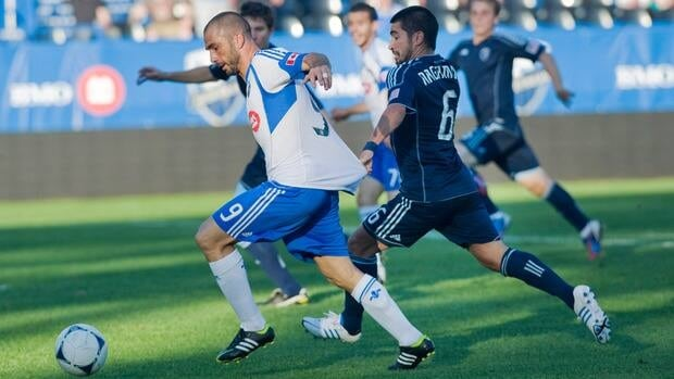 Sporting Kansas City's Paulo Nagamura, right, attempts to keep Impact forward Marco Di Vaio, left, within reach during the first half on Wednesday night in Montreal.