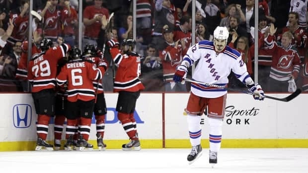 New York Rangers' Brian Boyle, right, skates away as members of the New Jersey Devils celebrate a goal by Travis Zajac during the first period on Monday night.