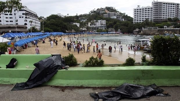 After the violent deaths of two Canadians in Mexico, tourists are asking if the country is safe to visit. Covered bodies are seen lying on a street next to the beach in the resort town of Acapulco, Aug. 16, 2011. The two men whose bodies are pictured here were shot dead by unidentified gunmen, according to local media.
