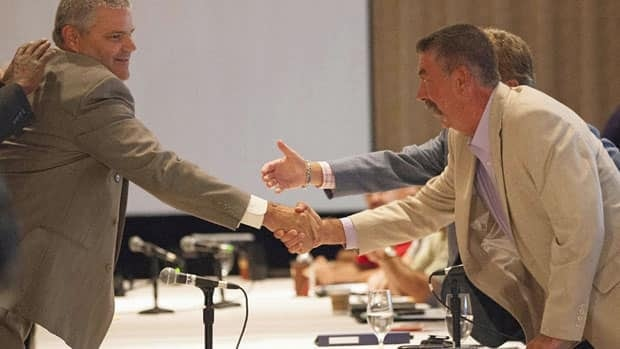 GM's General Director of Labour Relations, David Wenner, left, shakes hands with the head of the CAW's GM bargaining committee Chris Buckley, right, as contract talks open in Toronto Tuesday.