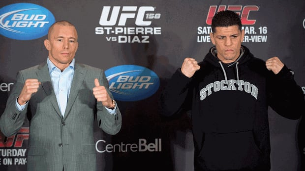 Georges St-Pierre, left, and Nick Diaz pose for the cameras following their news conference in Montreal on Thursday ahead of their UFC 158 title fight which takes place on Saturday.