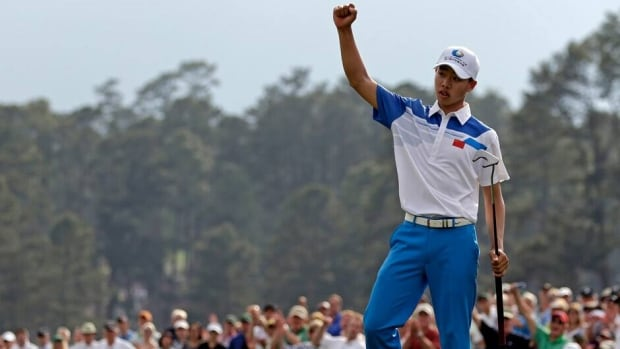 Amateur Guan Tianlang celebrates after a birdie putt on the 18th green during the first round of the Masters Thursday in Augusta, Ga.
