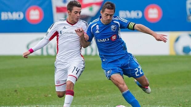 Montreal Impact's Davy Arnaud (22) challenges New England Revolution's Diego Fagundez for the ball during first half soccer action in Montreal on Saturday.
