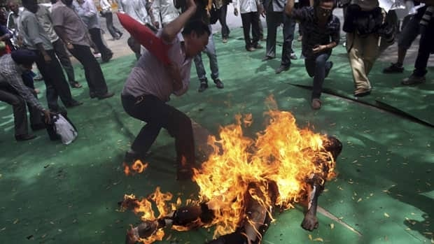 Tibetan exiles try to douse the flames from their comrade, Jamphel Yeshi, after he set himself on fire during a protest against the upcoming visit of Chinese President Hu Jintao to India in New Delhi March 26, 2012.