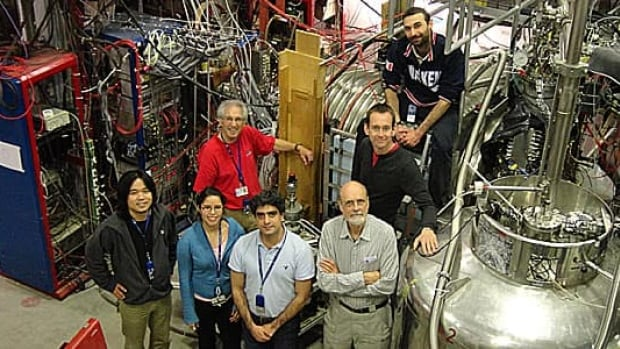 The ALPHA Canada team included (front row, left to right) Makoto Fujiwara, Andrea Gutierrez,  Mohammad Ashkezari, Walter Hardy, (middle row, left to right) Dave Gill, Mike Hayden and (back right) Simone Stracka. The horizontal silver cylinder is a superconducting magnet and the (anti)atom trap is inside. Antiprotons enter the apparatus from the left, and positrons enter from the right.