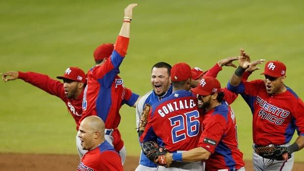 Puerto Rico's Andy Gonzalez, centre, celebrates with teammate Angel Pagan, 2nd right, soon after defeating the United States at the World Baseball Classic Friday in Miami.