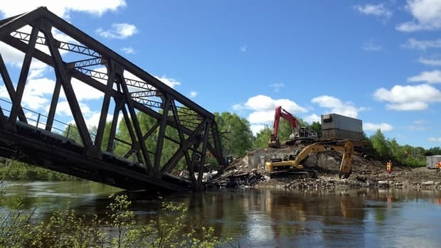Workers clear the site of a train derailment near Sudbury, Ont., on the Wanapitei River. The initial probe by CP has found one rail car had a wheel-bearing failure that caused the derailment just before the trestle bridge, which ended up collapsing.