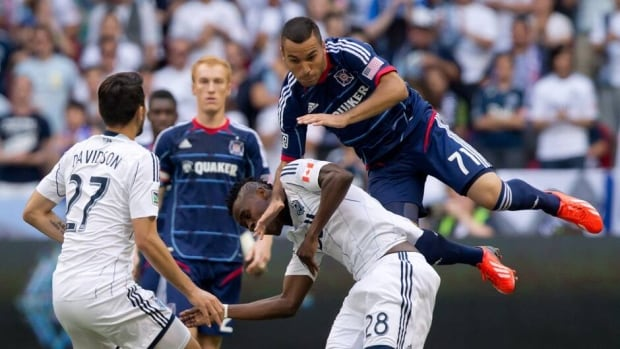 Chicago Fire's Alex Monteiro de Lima, right, falls on Vancouver Whitecaps' Gershon Koffie in Vancouver, B.C., on Sunday July 14, 2013.