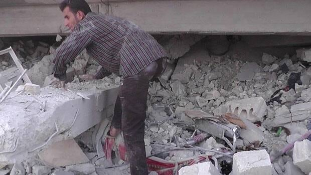 A Syrian man searches for people from under the rubble of a building that was destroyed by a Syrian force airstrike, at Kfar Nebel town, in Idlib province, northern Syria.