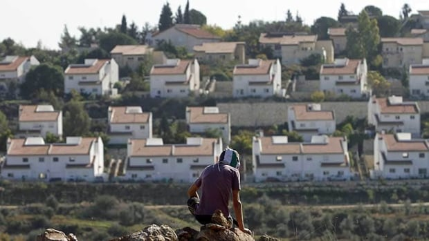 The Jewish settlement of Halamish is seen in the background as a masked Palestinian protester sits on a rock during clashes with Israeli security officers (unseen) at a protest against settlements in the West Bank village of Nabi Saleh, near Ramallah, on Friday.