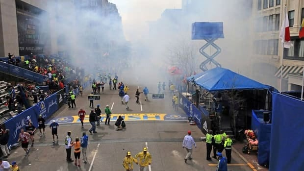 Smoke rises above the finish line. The explosions appear to have taken place at street level near a hotel and a storefront.