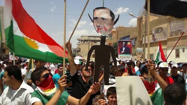 This citizen journalism image provided by Shaam News Network SNN purports to show anti-Syrian regime Kurdish protesters holding an effigy of Syrian President Bashar Assad as they wave their Kurdish flag during a demonstration in the northeastern town of Amouda, Syria, on Friday.